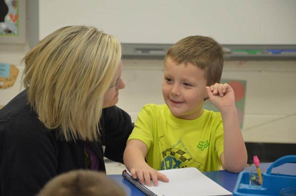 A kindergartner sharing his Leadership Notebook with his mom.